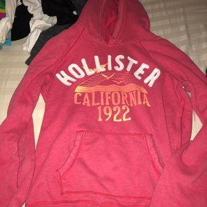 A reddish pink Hollister hoodie